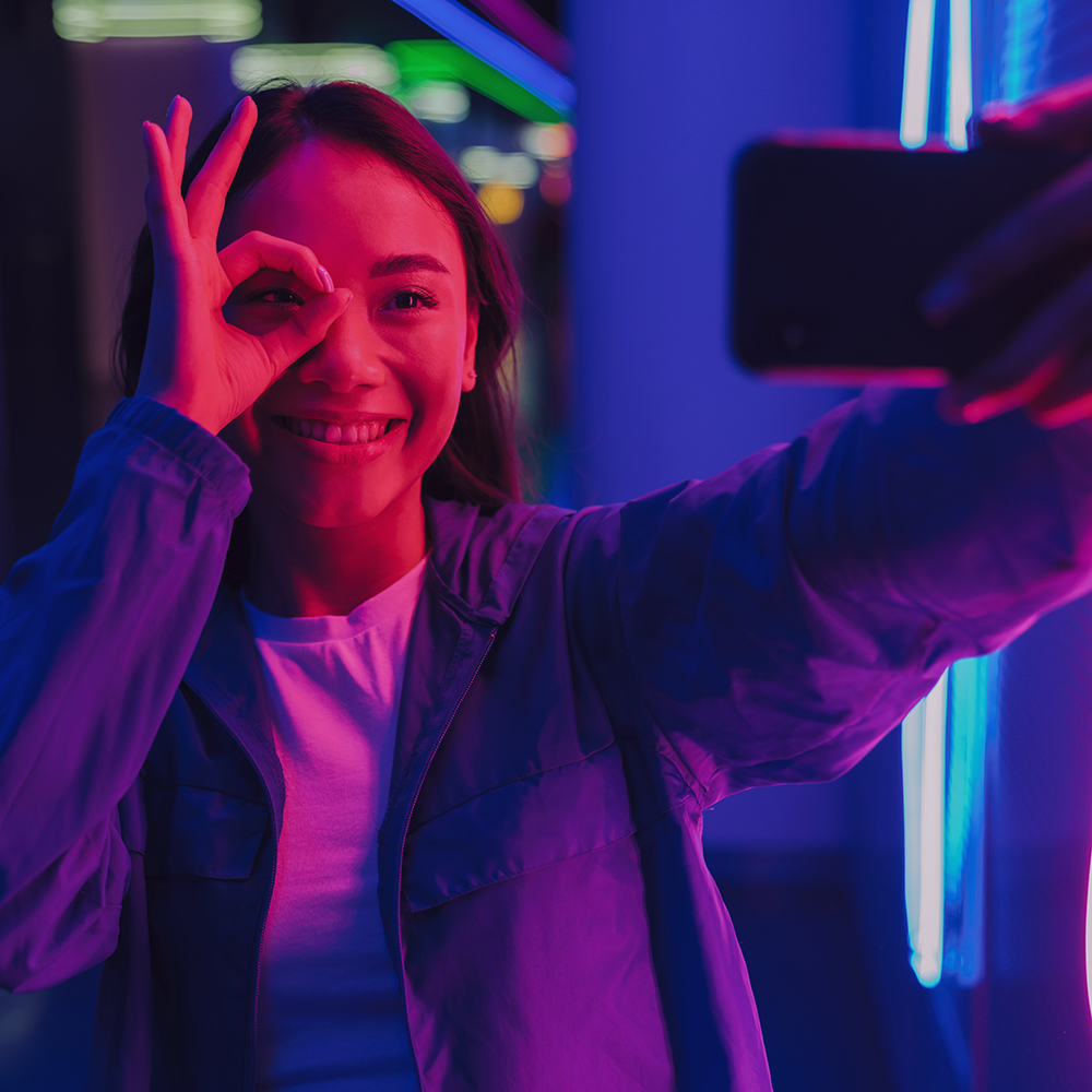 Young person makes a hand gesture on their face and takes a selfie in front of neon lights